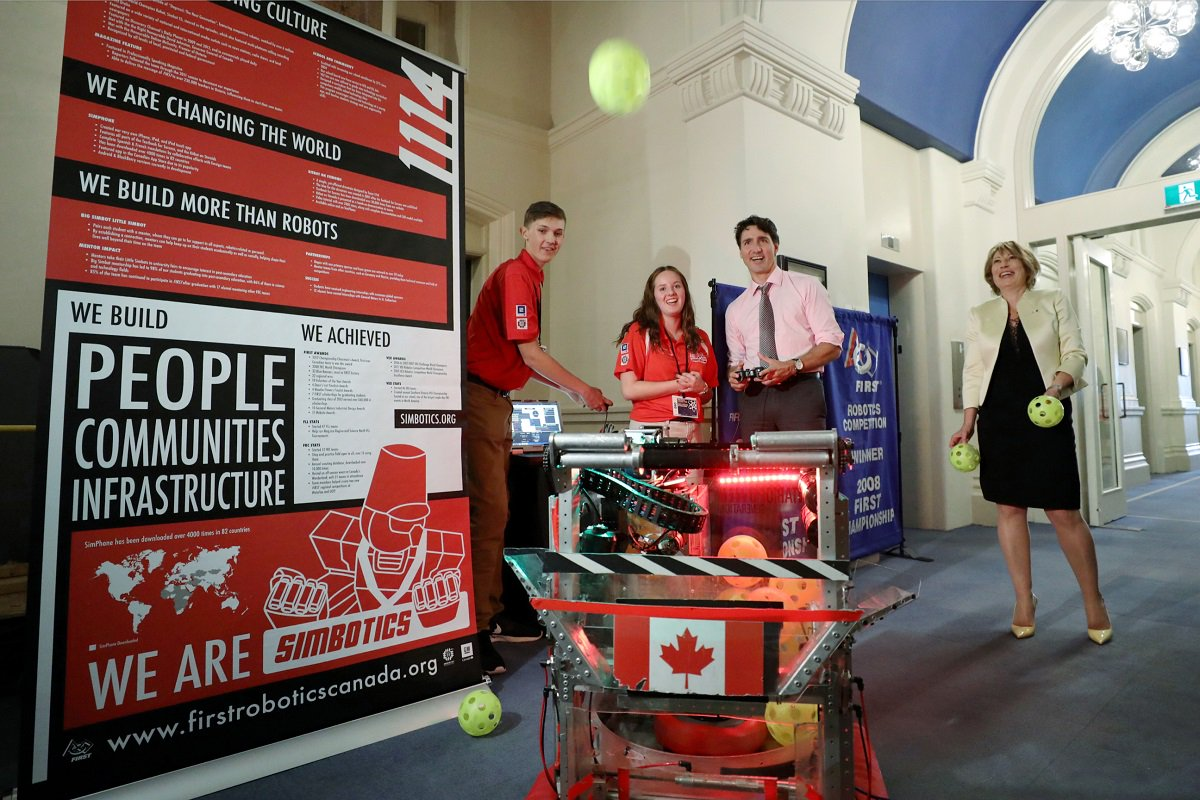 Justin Trudeau with Simbotics outreach banners